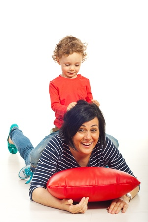 Toddler boy riding his mother and playing together home photo