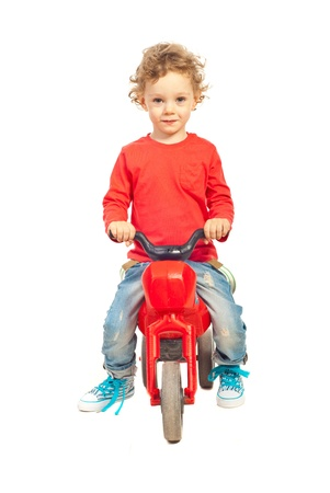 Smiling boy ride a plastic bike isolated onw hite background photo