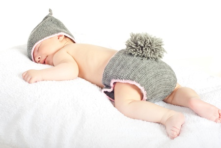 Sleeping newborn baby in knitted bunny costume isolated on white background photo