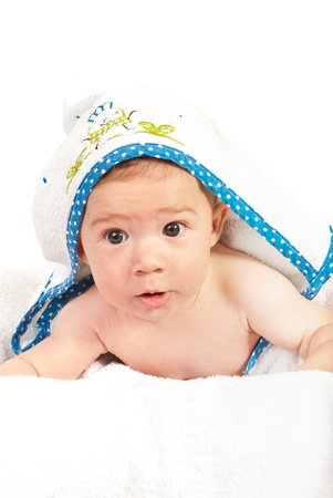 Curious baby boy in a bath towel laying  isolated on white background photo