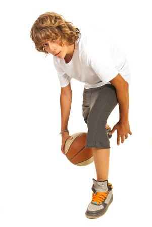 dribbling: Young boy dribbling basketball isolated on white background