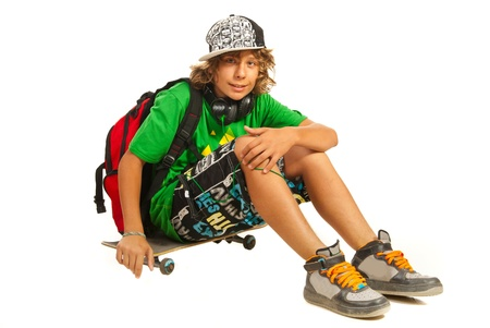 Modern teen schoolboy sitting on skateboard isolated on white background photo