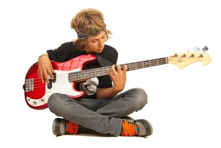 足を床に座っている十代の少年と白い背景に分離された低音ギターを弾く