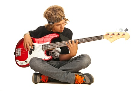 Teen boy sitting on floor with legs crossed and playing bass guitar isolated on white background