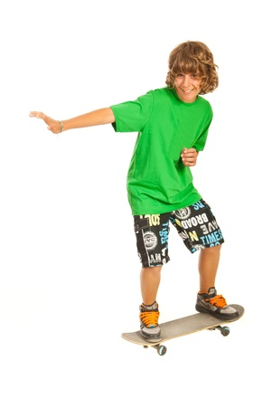 skateboarding tricks: Smiling teen boy skateboarder isolated on white background Stock Photo
