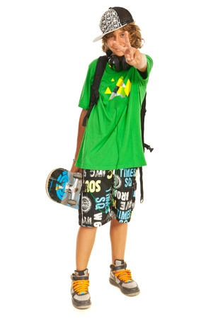 Cheerful teen boy with skateboard showing victory sign hand gesture isolated on white background photo