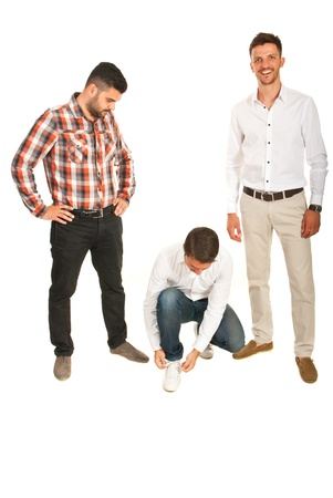 One businessman wondering and looking at a colleague who tying shoe laces and the other laughing isolated on white background photo