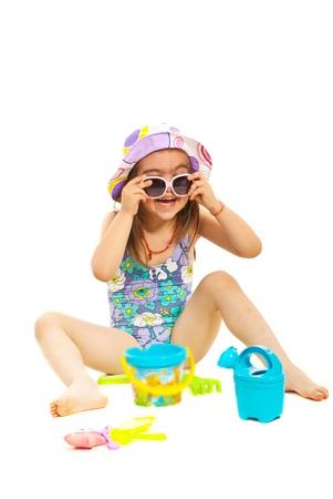 traje de bano: Ni�a en traje de ba�o con las gafas de sol que se divierten aislado en fondo blanco Foto de archivo