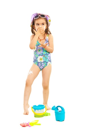child swimsuit: Preschooler girl applying sunblock cream isolated on white background