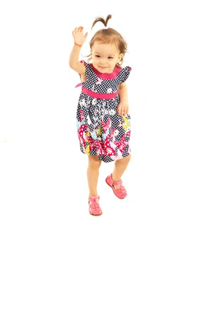 Little girl trying to jump isolated on white background photo