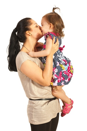 Mother kissing her toddler daughter isolated on white background photo