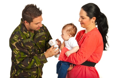come home: Mother and baby welcoming military father who gives to his child a fluffy bear toy isolated on white background