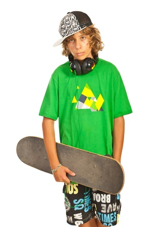 boy skater: Cool teen boy with headphones and cap holding skateboard isolated on white background
