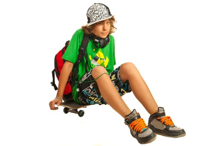 Teen schoolboy waiting or resting on skateboard isolated on white background photo