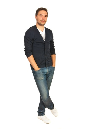 crossed legs: Cheerful casual man standing with hands to pockets jeans and legs crosed isolated onw hite background Stock Photo