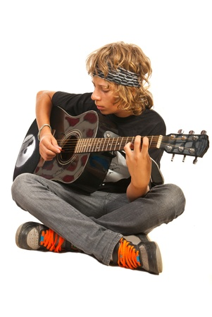 Teen boy playing accoustic guitar isolated on white background photo