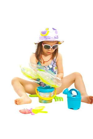 Girl sitting and playing with beach toys isolated on white background photo