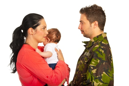 Mother holding baby boy and talking with her military husband isolated on white background photo