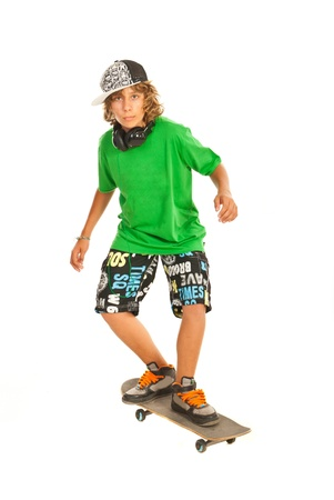 Cool teenager boy on skateboard isolated on white background photo