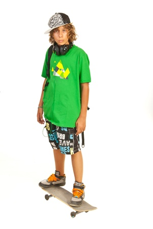 boy skater: Serious schoolboy teenager standing on skateboard isolated on white background