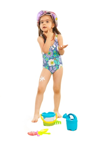 child swimsuit: Little girl in swimsuit applying sunscreen lotion on her face isolated onw hite background