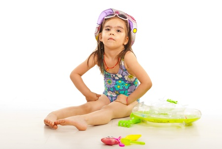 child swimsuit: Beach kid girl sitting with toys around  and looking at camera