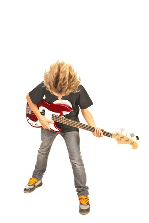 Teenager boy playing bass guitar and flipping hair isolated on white background photo