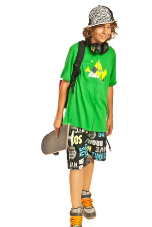 Schoolboy teen with skateboard isolated on white background photo