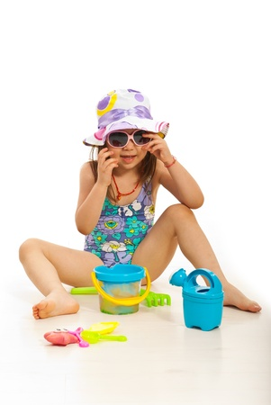 Funny girl with hat and sunglasses playign with beach toys photo