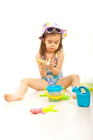 child swimsuit: Girl using sunblock lotion and sitting down with beach toys around her