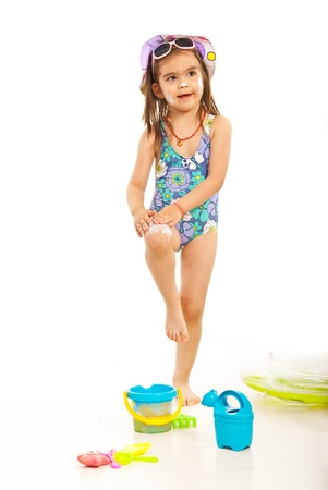 child swimsuit: Girl applying sunblock lotion on her legs and face