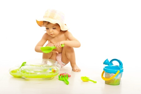 Cute toddler girl playing with beach toys isolated on white background photo