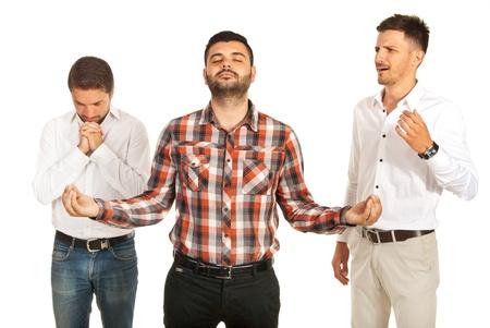 personas orando: Un hombre de oración, otro hombre medita y otro mirando ellos y estar asustado y sorprendido aislado sobre fondo blanco Foto de archivo