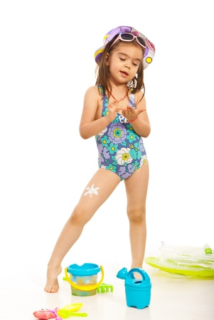 child swimsuit: Cheerful little girl apply sunscreen lotion on her body against white background Stock Photo
