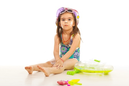 child swimsuit: Little girl apply sunsxreen lotion on her body and sitting down on floor Stock Photo