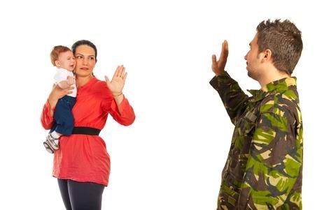 Moeder bedrijf huilende baby en afscheid te nemen van haar militaire man die terug gaat naar het leger op een witte achtergrond Stockfoto