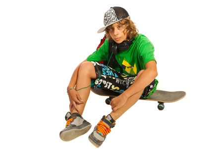 Teen boy sitting on skateboard isolated on white background photo