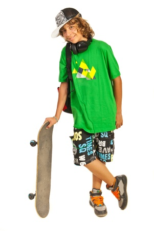 Cheerful schoolboy teen boy with skateboard isolated on white background photo
