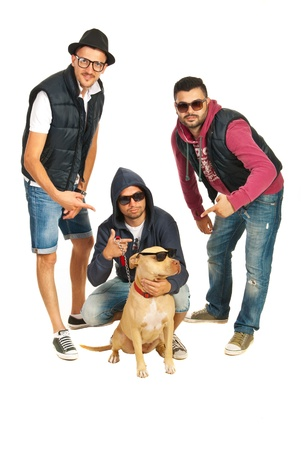 Funky group of three rappers pointing to their pitbull dog with sunglasses isolated on white background photo