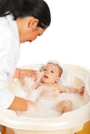 personas banandose: Lavar su beb� reci�n nacido en una ba�era con espuma Madre Foto de archivo