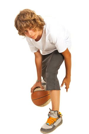 dynamic activity: Teenager boy dribbling basketball isolated on white background