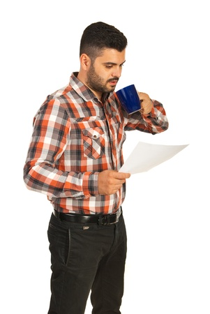 Business man drinking coffee and reading a paper isolated on white background photo