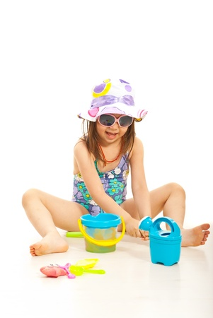 Cheerful girl playing with beach toys isolated on white background photo