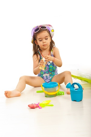 child swimsuit: Girl opening sunblock lotion bottle and sitting down with beach toys