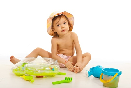 Beauty toddler girlplaying with beach toys agaisnt white wall photo