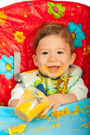 messy eater: Happy baby sitting in chair and eating vegetables puree