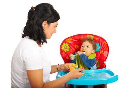 messy eater: Mother giving puree to her baby boy and having conversation against white background Stock Photo