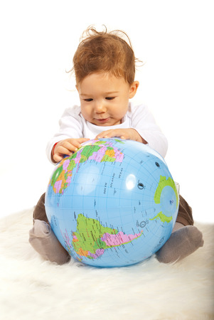 Baby boy sitting on fur blanket and searching on a world globe photo
