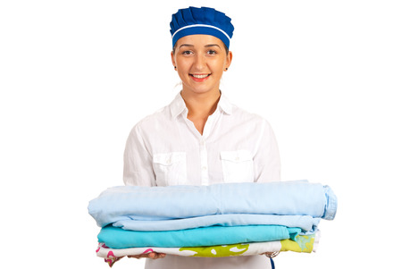 Smiling hotel maid holding stack of sheet to making bed isolated on white background Stock Photo - 22548148