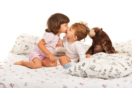 Toddler girl kissing a baby boy and sitting together in bed with teddy bear photo
